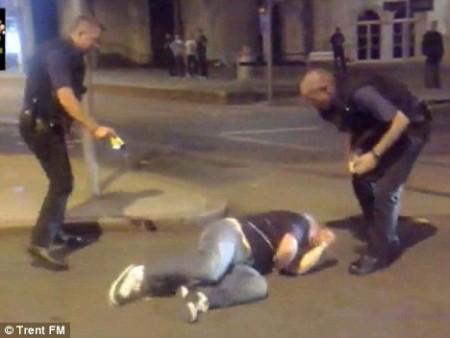 As fotos mostram o oficial à esquerda atingindo com taser o suspeito que agoniza no chão enquanto o seu colega fica para trás e assiste