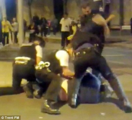 O agente policial à direita do quadro tem o seu braço direito puxado e erguido para trás como se  socasse o suspeito três vezes na cabeça